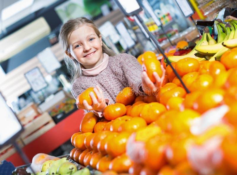 Niña sonriente alegre que compra los mandarines dulces fotos de archivo