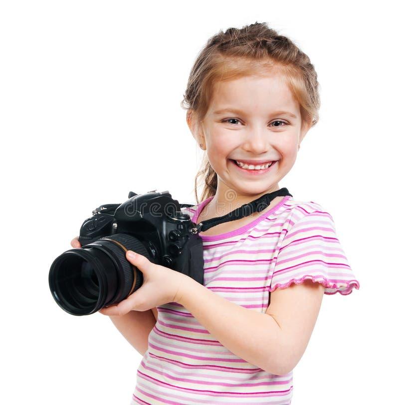 Niña sonriente bonita que sostiene la lente grande de la cámara profesional aislada fotos de archivo