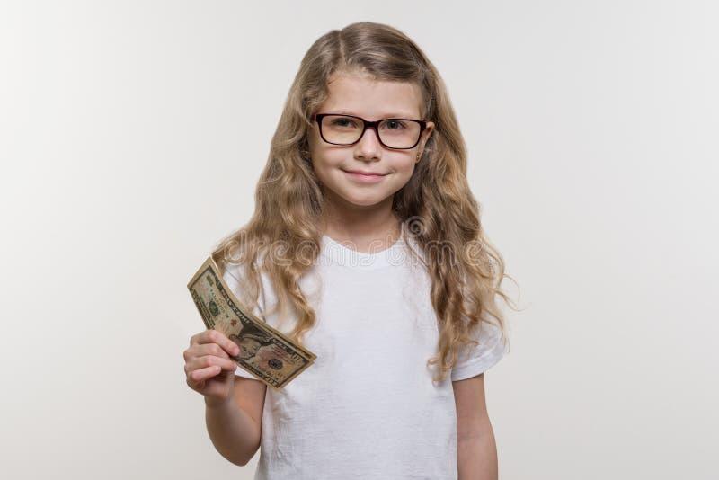 Niña sonriente con efectivo, dinero, finanzas y el concepto de gente imágenes de archivo libres de regalías