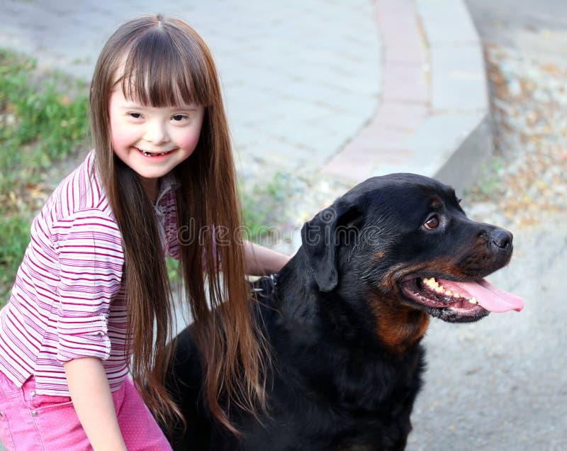 Niña sonriente con el perro imagen de archivo