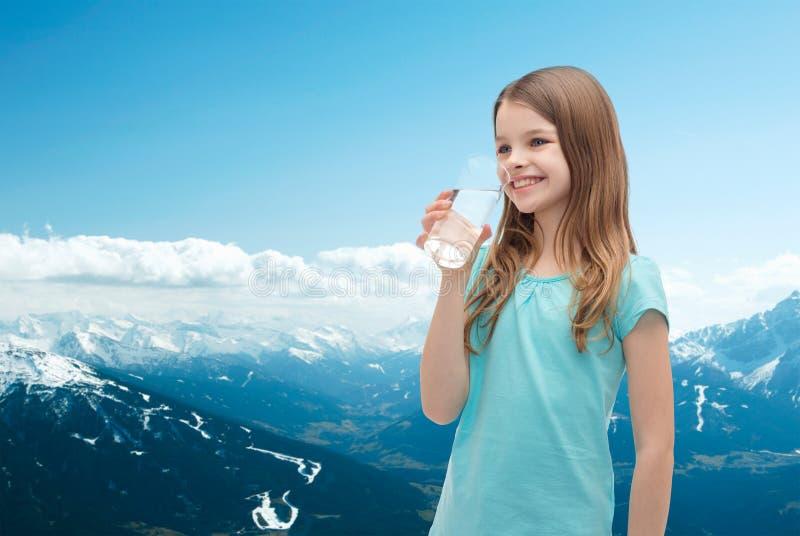 Niña sonriente con el vidrio de agua foto de archivo libre de regalías