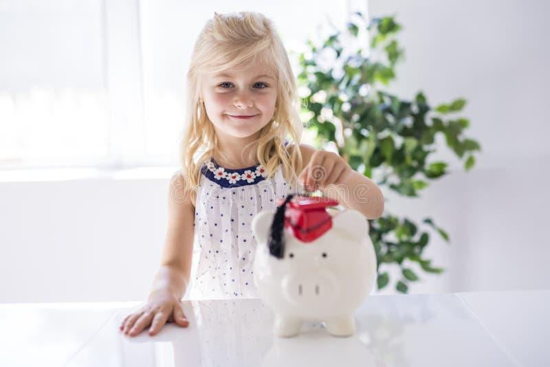 Niña sonriente con la hucha y el dinero en casa fotos de archivo libres de regalías