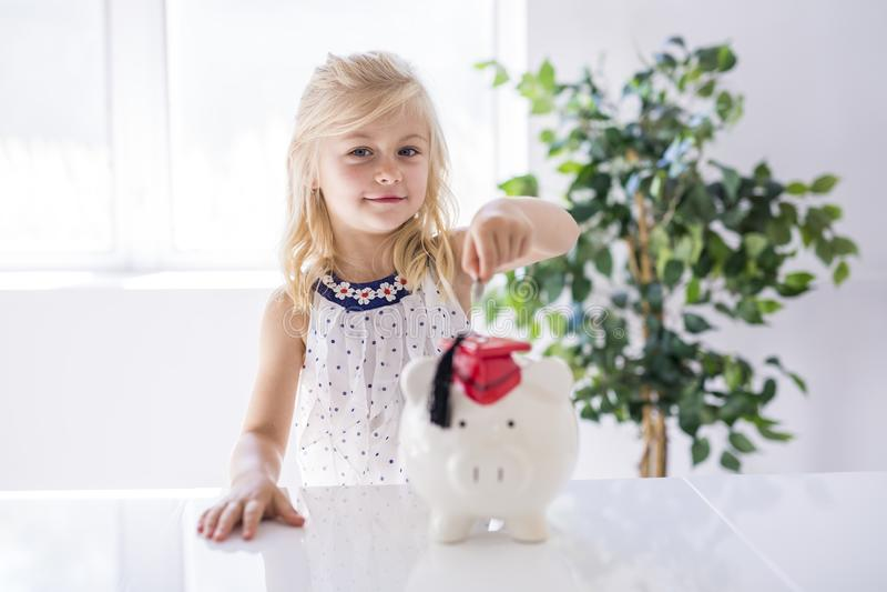 Niña sonriente con la hucha y el dinero en casa imagen de archivo