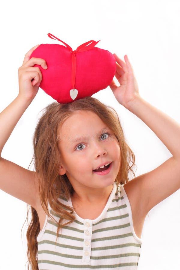 Niña sonriente con un corazón rojo imagenes de archivo