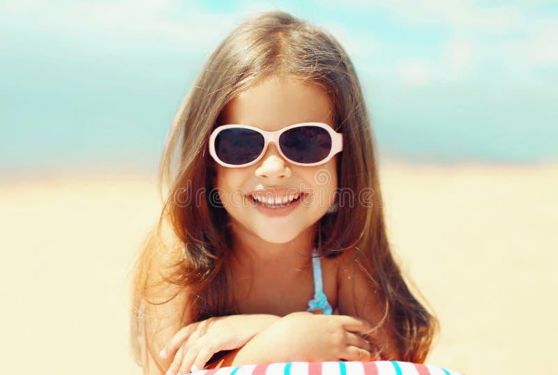Niña sonriente del niño del retrato del primer del verano que miente en la playa imagen de archivo