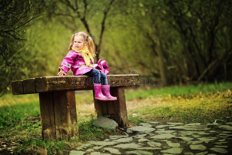 Niña sonriente en el día lluvioso en el parque fotografía de archivo libre de regalías
