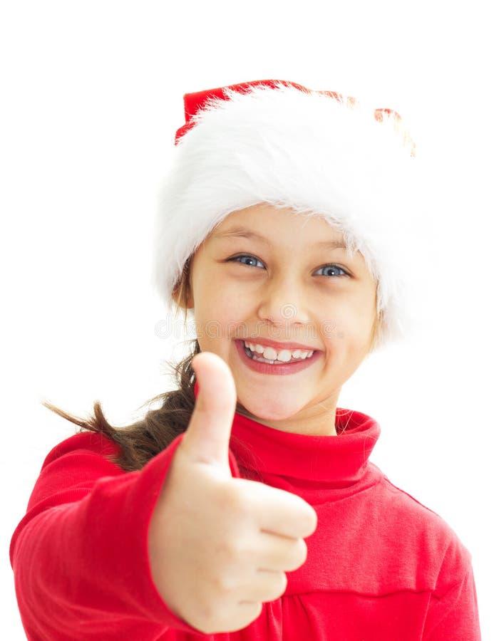 niña sonriente en el sombrero de Papá Noel que muestra el pulgar fotografía de archivo libre de regalías