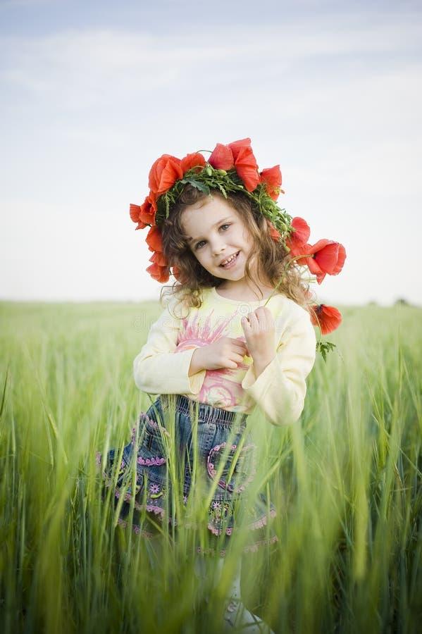 Niña sonriente en guirnalda floral foto de archivo libre de regalías