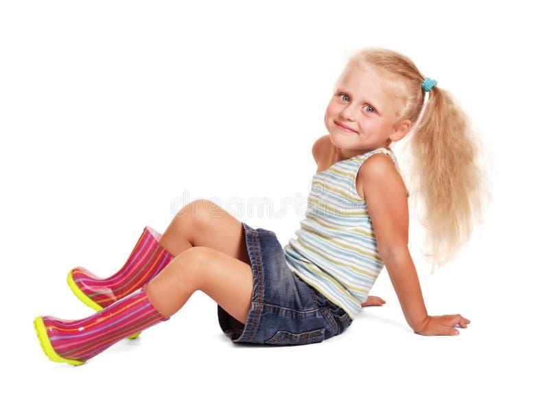 Niña sonriente en la falda, blusa, el sentarse de las botas de goma aislada imagenes de archivo