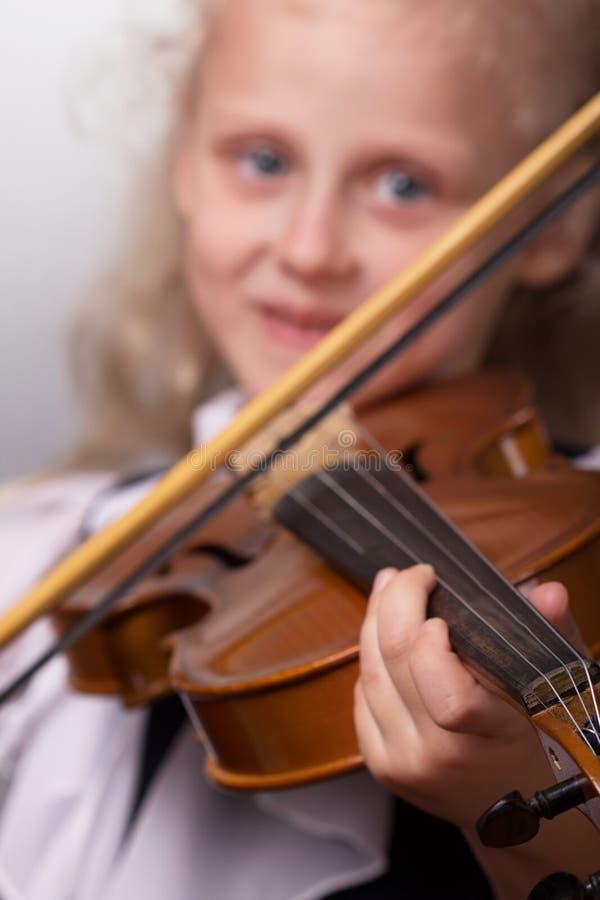 Niña sonriente en la ropa elegante que toca el violín imagen de archivo libre de regalías