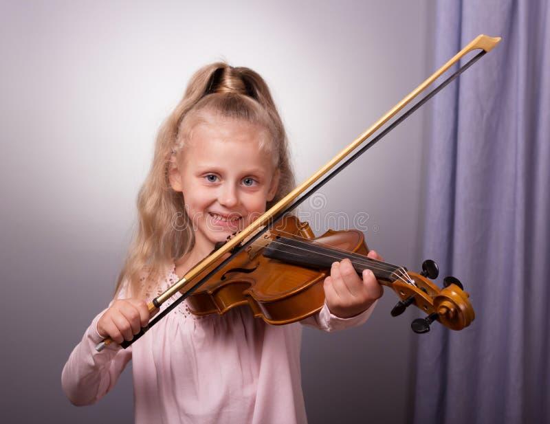 Niña sonriente en la ropa elegante que toca el violín fotografía de archivo libre de regalías