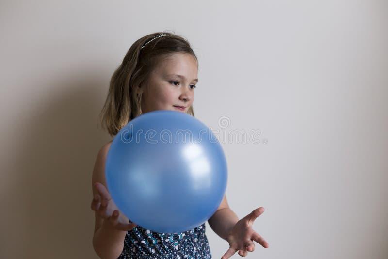 Niña sonriente en perfil de tres cuartos con la flotación azul del globo fotos de archivo libres de regalías