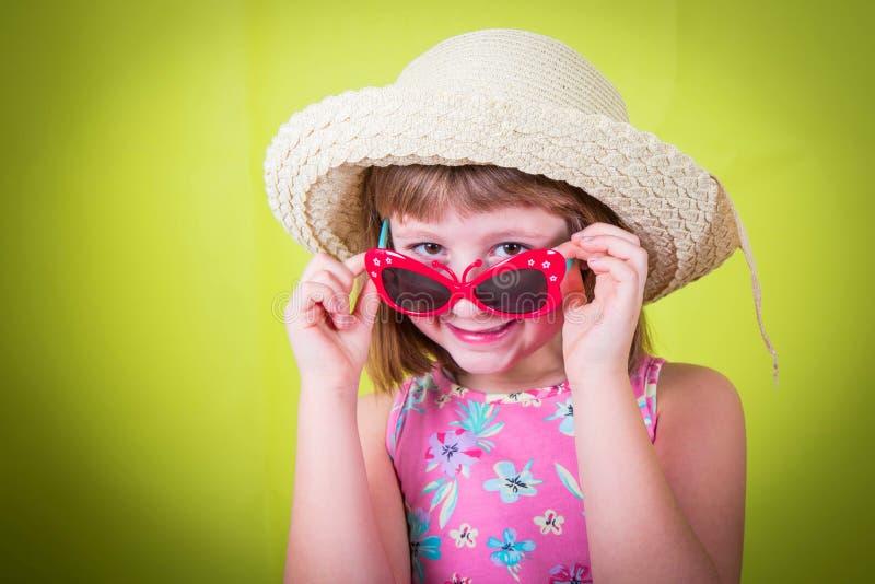 Niña sonriente en sombrero de paja y gafas de sol foto de archivo libre de regalías