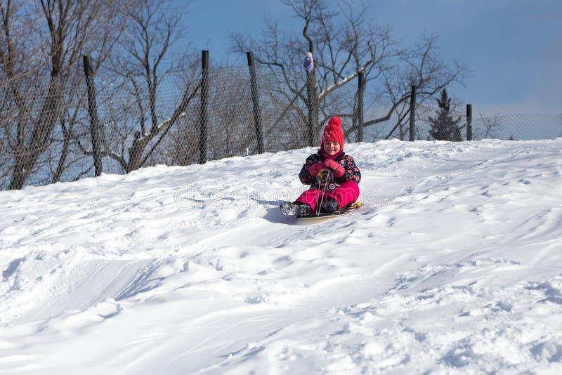 Niña sonriente en su traje de esquí que resbala abajo de una pequeña nieve imagen de archivo libre de regalías