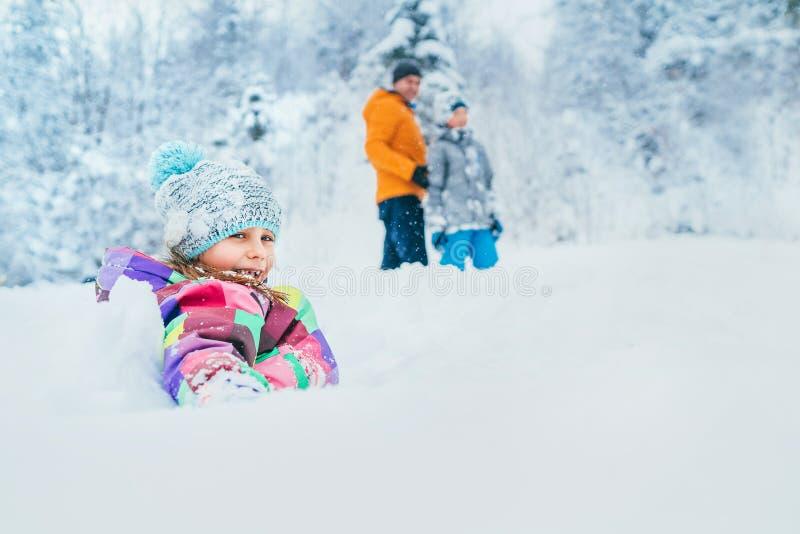 Niña sonriente feliz que se sienta en nieve profunda cuando ella que camina con la familia en bosque nevoso del invierno fotos de archivo libres de regalías