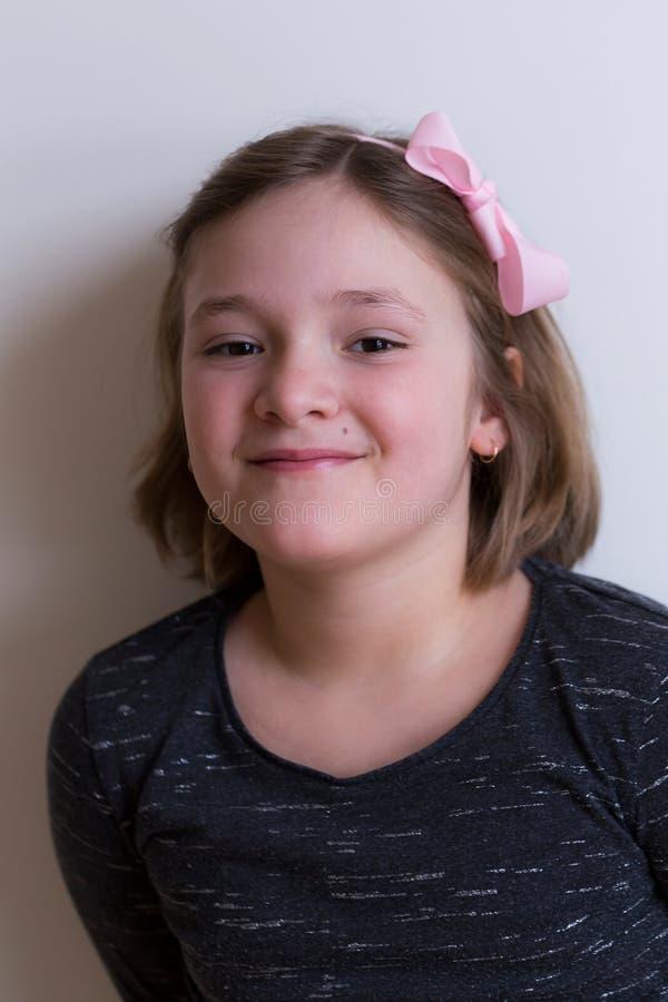 Niña sonriente hermosa con el pelo meneado corto y el hairband rosado foto de archivo
