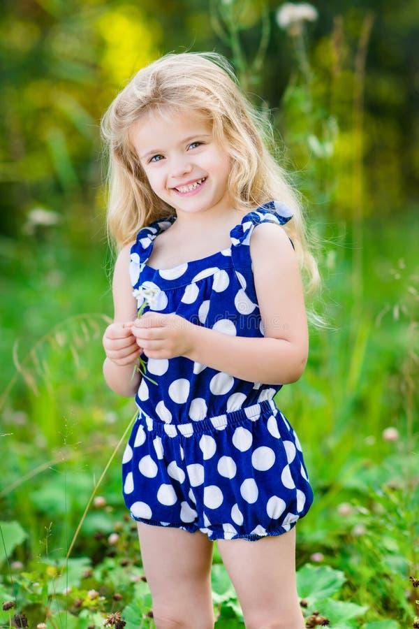 Niña sonriente hermosa con el pelo rizado rubio largo imágenes de archivo libres de regalías