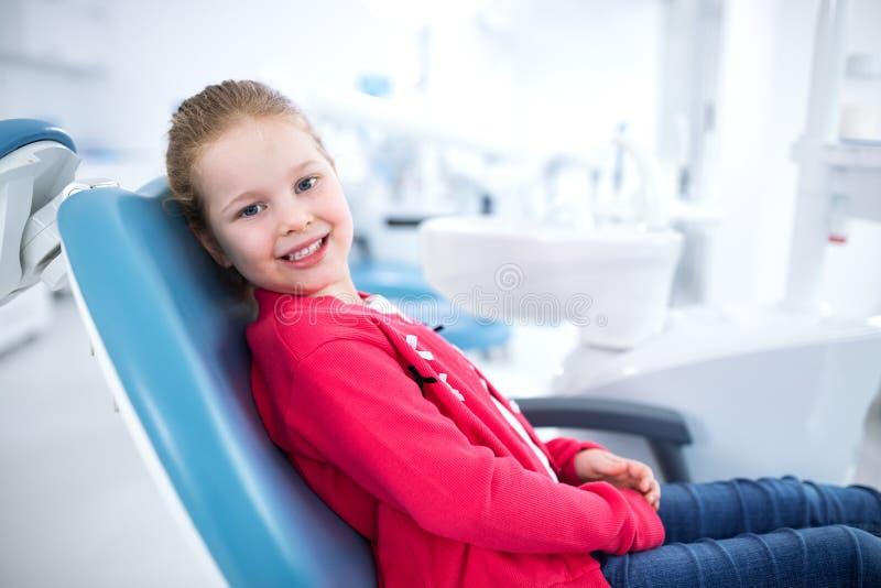 Niña sonriente hermosa en oficina dental imagen de archivo libre de regalías