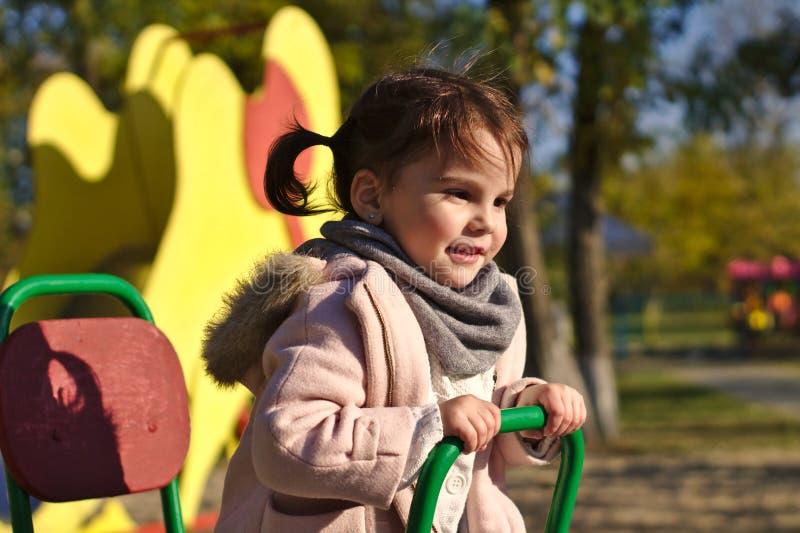 Niña sonriente hermosa en parque del otoño foto de archivo