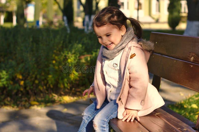 Niña sonriente hermosa en parque del otoño imagen de archivo libre de regalías