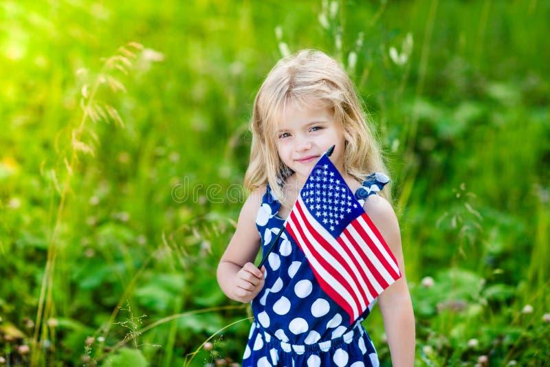 Niña sonriente linda con el pelo rubio que sostiene la bandera americana foto de archivo