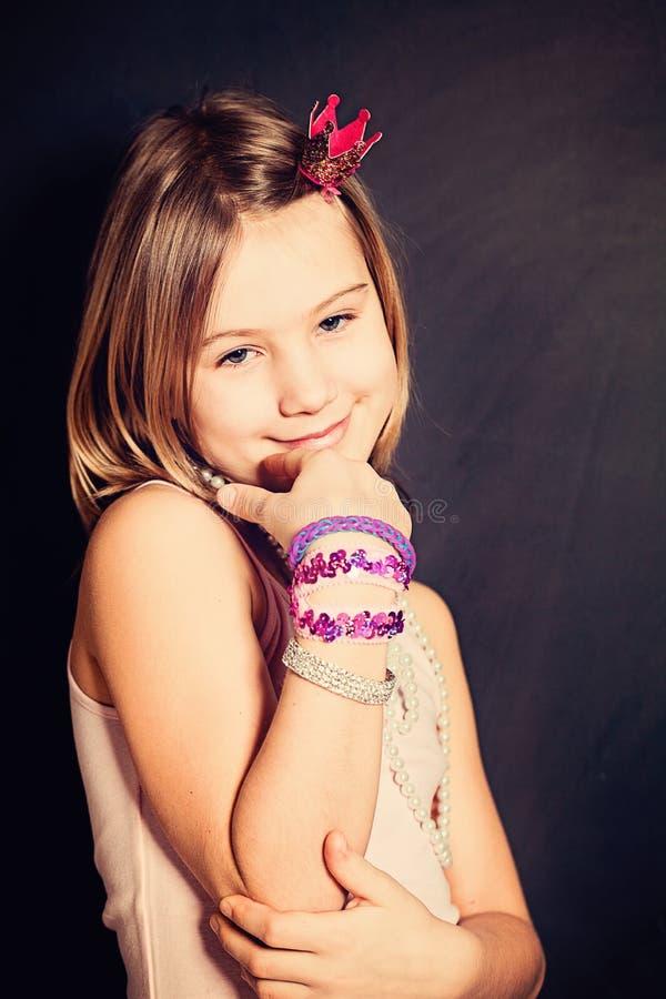 Niña sonriente linda con la joyería o la joya de los niños imagen de archivo