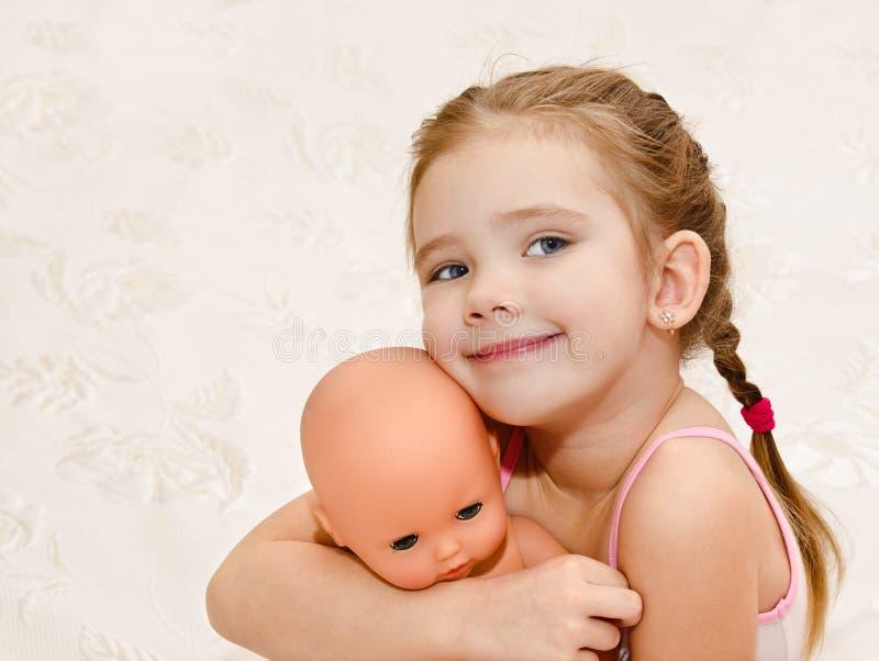 Niña sonriente linda con la muñeca fotografía de archivo libre de regalías