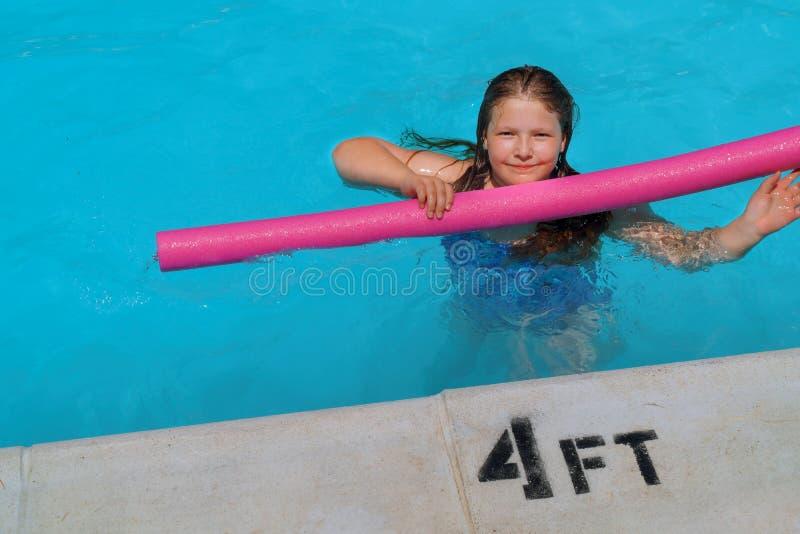 Niña sonriente linda en piscina de las vacaciones de verano fotos de archivo