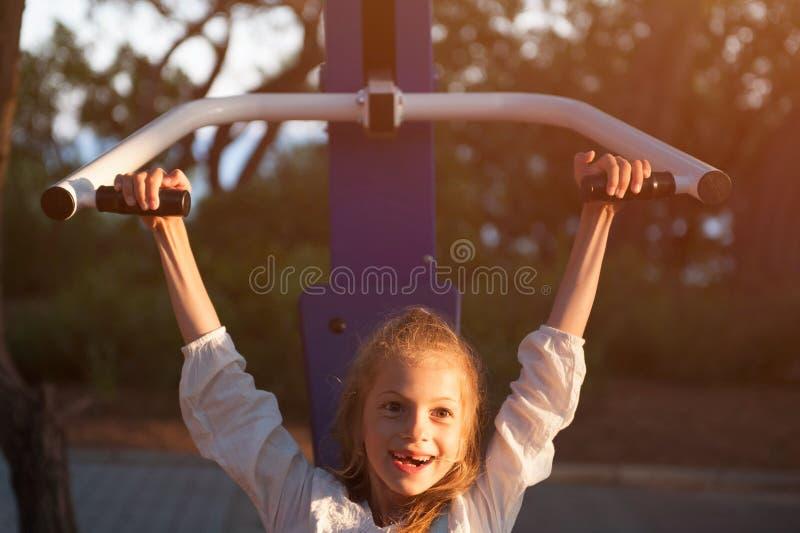 Niña sonriente linda que se sienta en entrenamiento al aire libre del equipo del instructor fotos de archivo