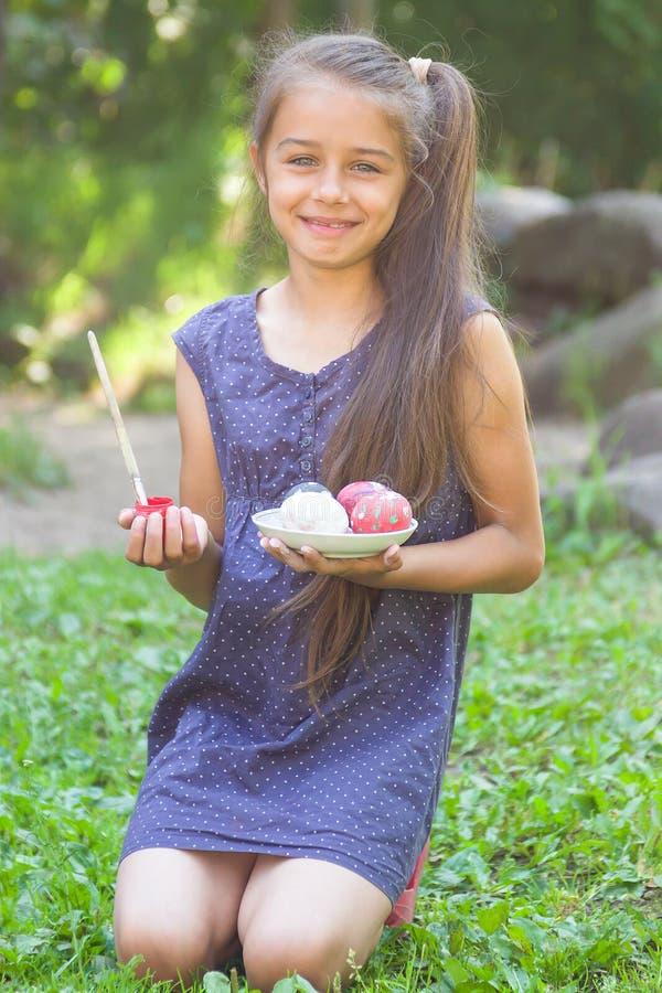 Niña sonriente linda que se sienta en una hierba verde y que sostiene los huevos de Pascua y paintbrus pintados foto de archivo libre de regalías