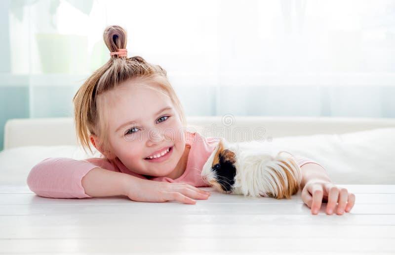 Niña sonriente que abraza el conejillo de Indias foto de archivo libre de regalías