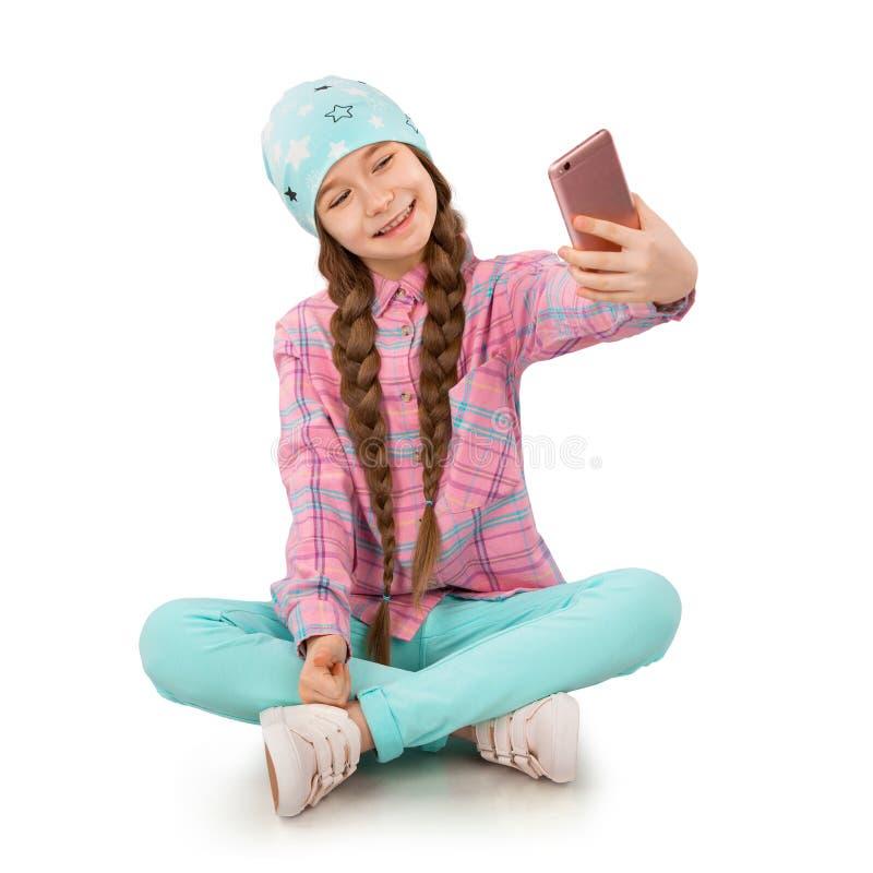 Niña sonriente que celebra el teléfono móvil y la fabricación del selfie en el fondo blanco imagenes de archivo