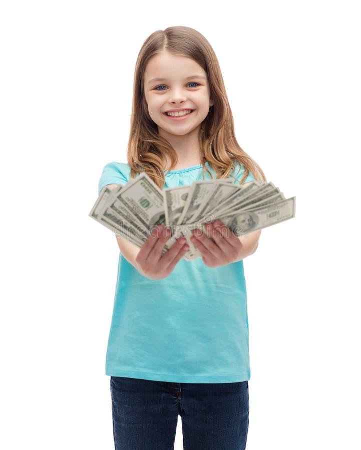 Niña sonriente que da el dinero del efectivo del dólar imágenes de archivo libres de regalías