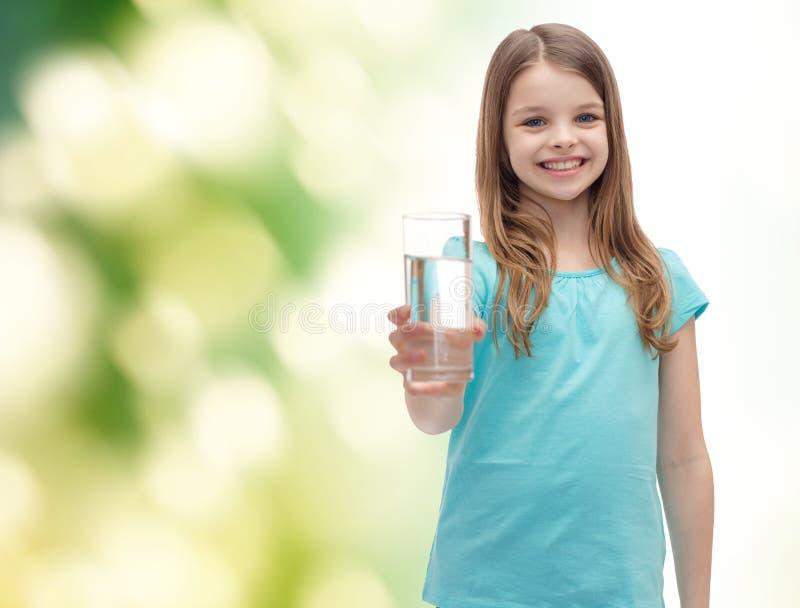 Niña sonriente que da el vidrio de agua fotos de archivo libres de regalías