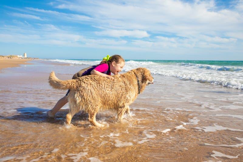 Niña sonriente que juega con un perro en la orilla de la playa fotografía de archivo libre de regalías
