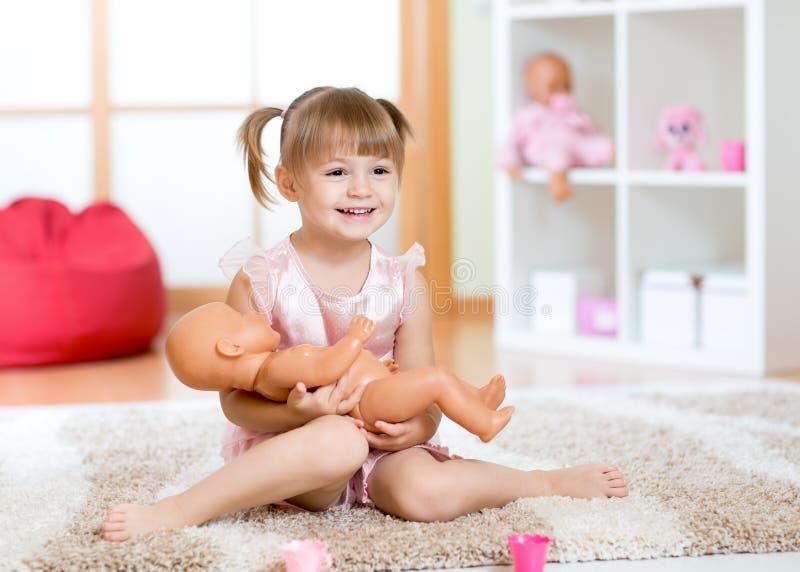 Niña sonriente que juega con una muñeca en casa foto de archivo libre de regalías