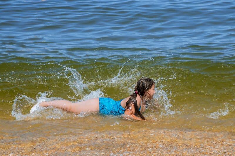 Niña sonriente que lo pone en agua en la costa de la playa el océano fotografía de archivo
