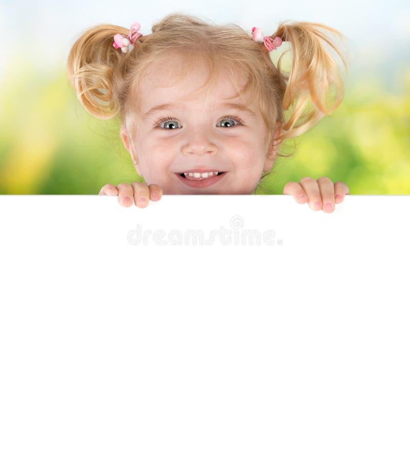 Niña sonriente que mira a escondidas detrás de un tablero fotografía de archivo