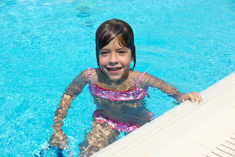 Niña sonriente que mira la cámara en una piscina al aire libre foto de archivo