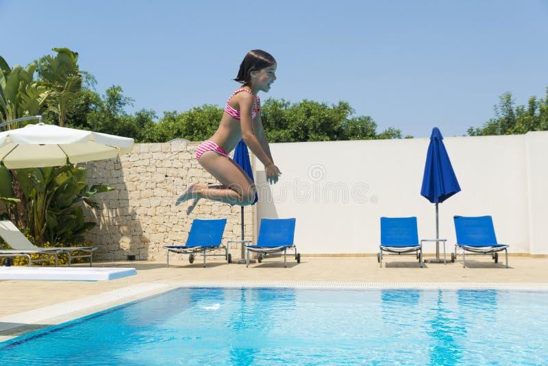 Niña sonriente que salta en bomba en una piscina al aire libre foto de archivo libre de regalías