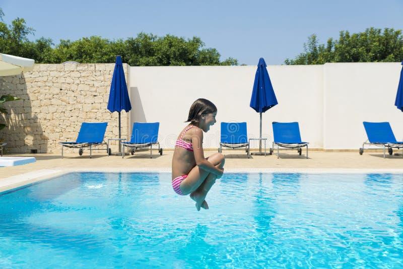 Niña sonriente que salta en bomba en una piscina al aire libre fotos de archivo libres de regalías