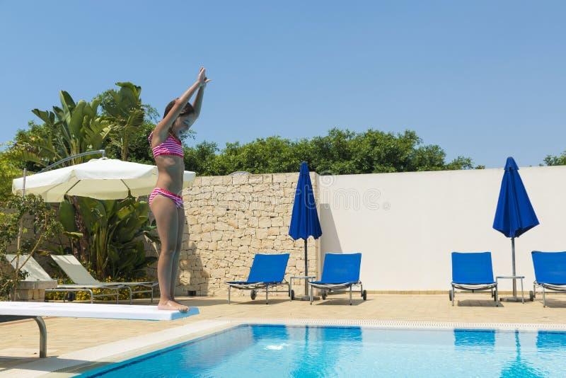 Niña sonriente que salta en una piscina al aire libre en verano foto de archivo libre de regalías