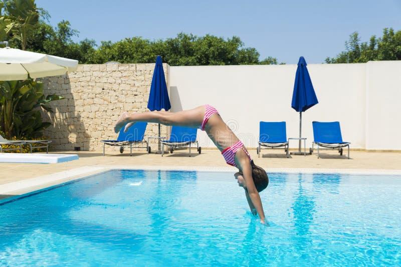 Niña sonriente que salta en una piscina al aire libre en verano fotos de archivo libres de regalías