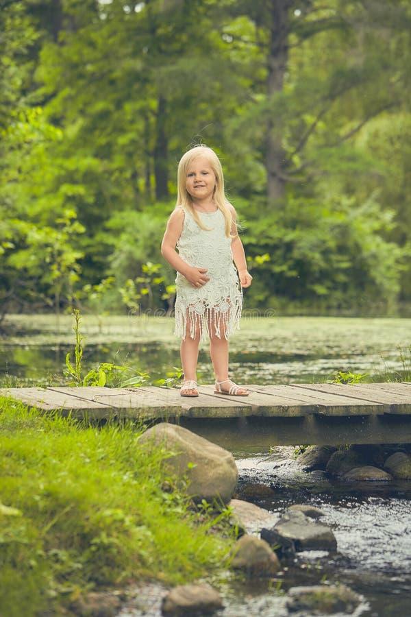 Niña sonriente que se coloca en el puente en verano imagenes de archivo