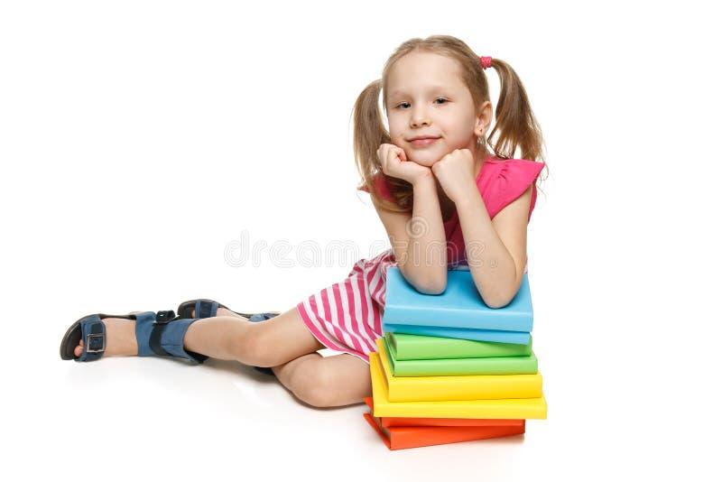 El inclinarse que se sienta de la niña en la pila de libros fotografía de archivo