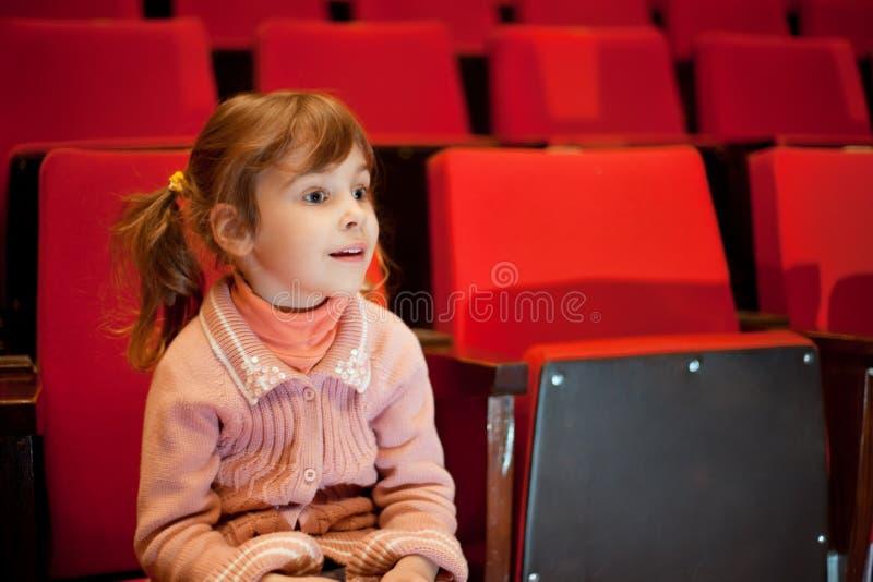Niña sonriente que se sienta en las butacas en el cine fotos de archivo