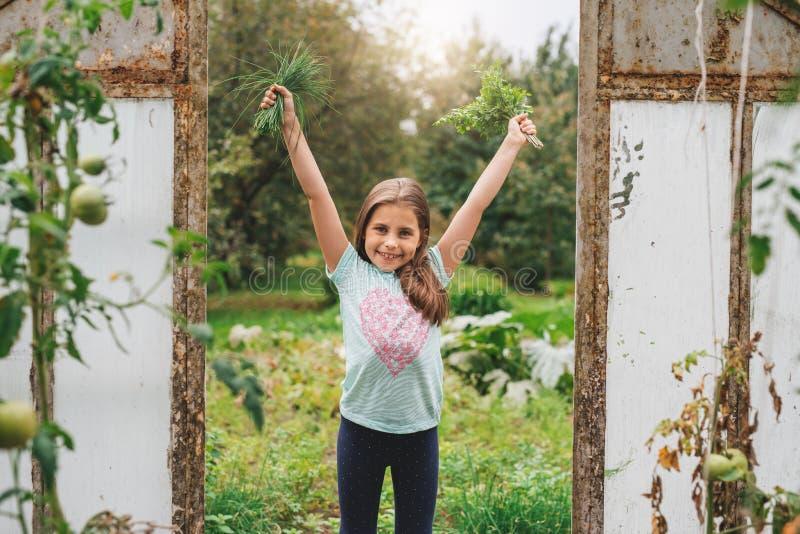 Niña sonriente que sostiene las hierbas afuera imagenes de archivo