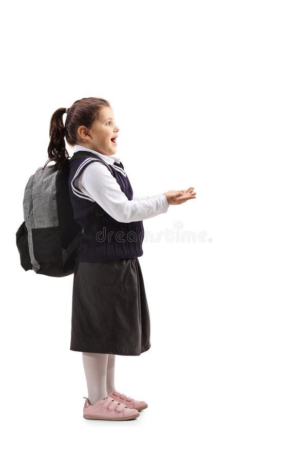 Niña sorprendida en un uniforme escolar que lleva a cabo sus manos en f imagenes de archivo