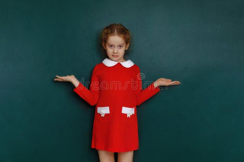 Niña sorprendida en vestido rojo cerca de la pizarra en sala de clase imagen de archivo
