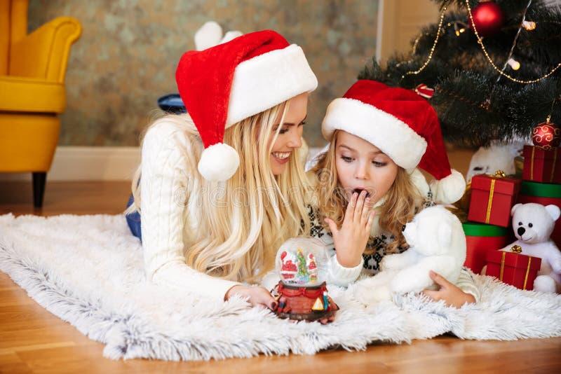 Niña sorprendida que consigue el juguete de la bola de la nieve de su whil de la madre fotos de archivo